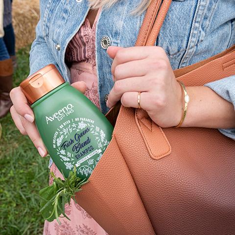 Woman holding Aveeno Fresh Greens Shampoo